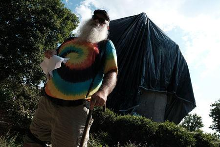 John Miska reacts after being confronted by police while he attempted to remove the black tarp with which the City of Charlottesville covered the statue of Confederate General Robert E. Lee in Charlottesville, Virginia, U.S., August 23, 2017. REUTERS/Justin Ide