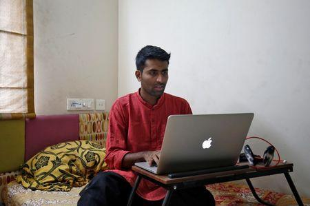 Akhilesh Godi, one of the petitioners challenging India's ban on homosexuality, checks his laptop as he poses inside his house in Bengaluru