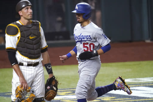 Los Angeles Dodgers' Mookie Betts (50) scores on a throwing error by San Diego Padres' Fernando Tatis Jr. during the third inning in Game 3 of a baseball National League Division Series Thursday, Oct. 8, 2020, in Arlington, Texas. At left is San Diego Padres catcher Jason Castro. (AP Photo/Tony Gutierrez)