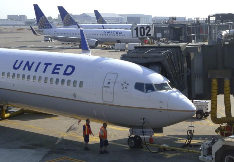 File photo: Two ground crew members walk past a United Airlines airplane as it sits at a gate at Newark Liberty International Airport