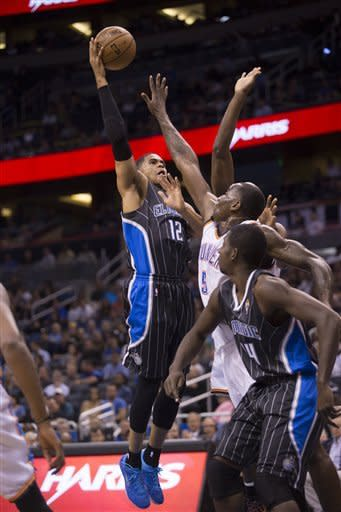 CORRECTS TO MAGIC'S ANDREW NICHOLSON NOT JAMEER NELSON - Orlando Magic's Tobias Harris (12) over Oklahoma City Thunder's Kendrick Perkins (5) as Magic's Andrew Nicholson watches during the first half of an NBA basketball game on Friday, March 22, 2013, in Orlando, Fla. (AP Photo/Willie J. Allen Jr.)