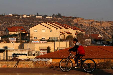 FILE PHOTO: A boy rides his bicycle past houses in the Israeli settlements of Ofra, in the occupied West Bank