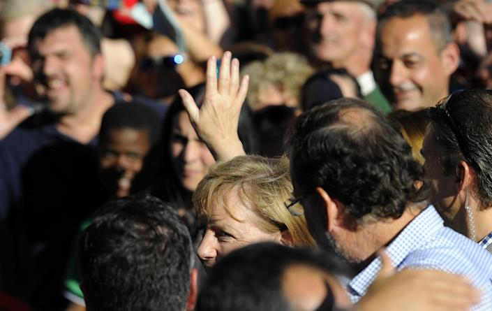 German Chancellor Angela Merkel salutes people upon her arrival at the Obradoiro Square in Santiago de Compostela, on August 24, 2014 (AFP Photo/Miguel Riopa )