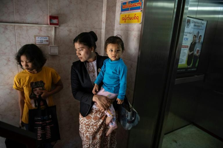 Hla Hla Yee holds her daughter before a meeting at the Gender Equality Network office in Yangon