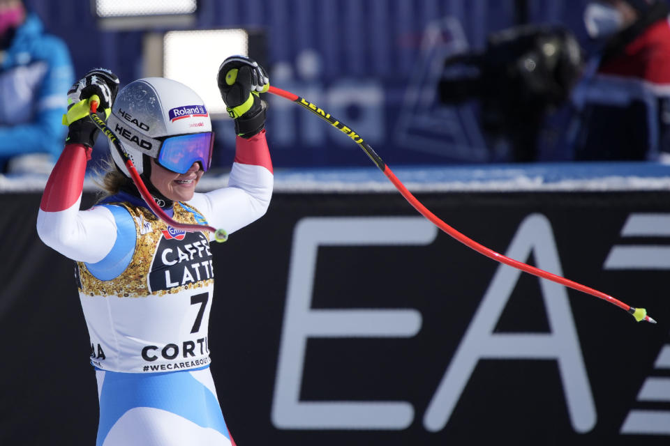 Switzerland's Corinne Suter celebrates as she gets to the finish area after completing the women's downhill, at the alpine ski World Championships in Cortina d'Ampezzo, Italy, Saturday, Feb. 13, 2021. (AP Photo/Giovanni Auletta)