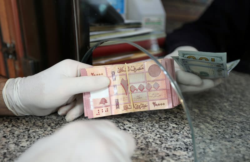 FILE PHOTO: A customer wearing gloves holds Lebanese pounds at a currency exchange store in Beirut