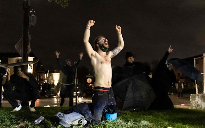 """Demonstrators shout """"Don't shoot"""" at the police after curfew as they protest the death of Daunte Wright"""