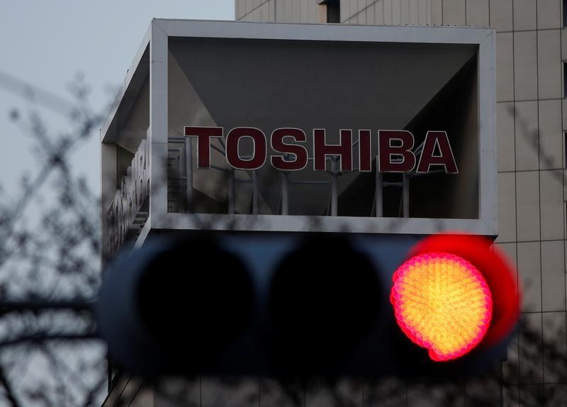 The logo of Toshiba Corp is seen behind a traffic light at the company's headquarters in Tokyo