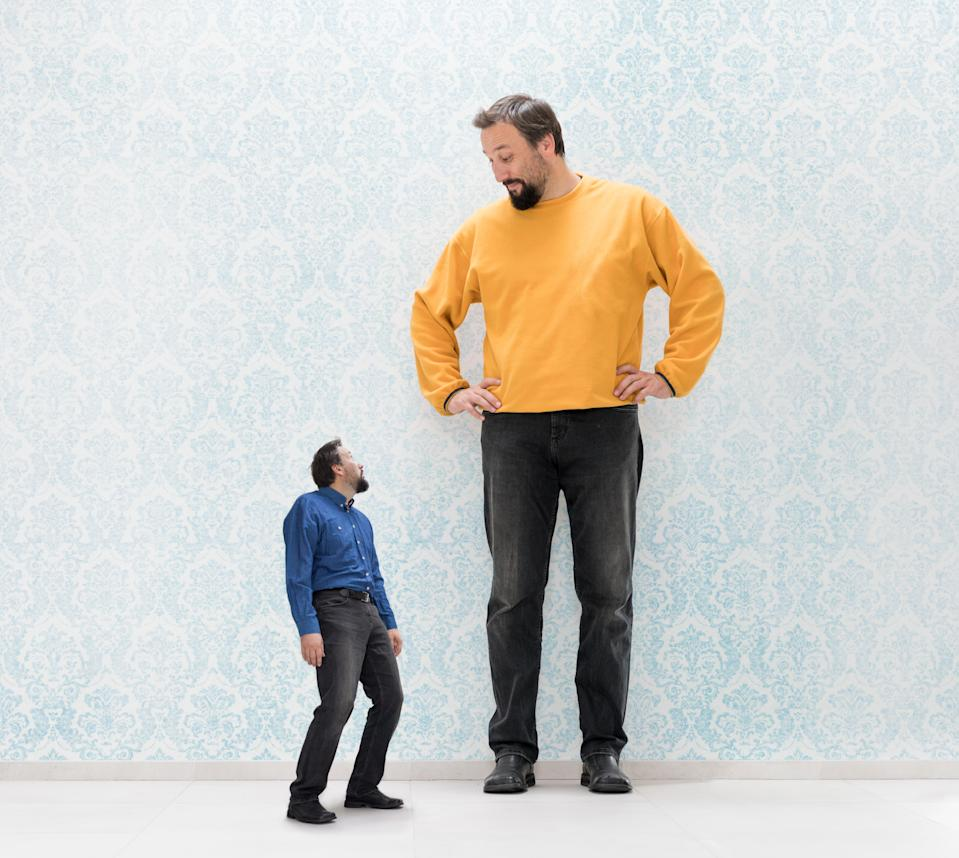 Very big and very small man on vintage wallpaper wall concept