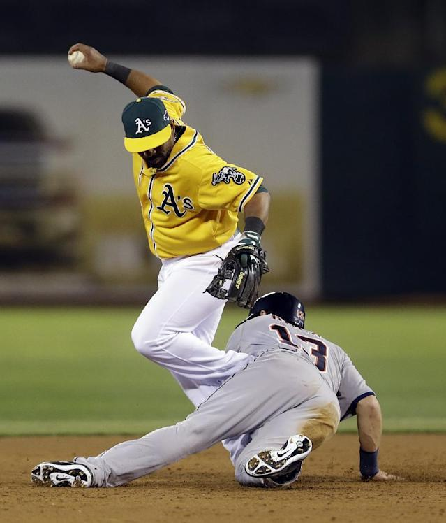Oakland Athletics second baseman Alberto Callaspo, left, forces out Detroit Tigers Alex Avila on a ground ball hit by Omar Infante in the sixth inning of Game 5 of an American League baseball division series in Oakland, Calif., Thursday, Oct. 10, 2013. (AP Photo/Marcio Jose Sanchez)