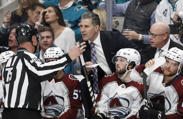 Colorado Avalanche head coach Jared Bednar, center, talks with an official after a goal by Colin Wilson was called back for a penalty during the second period of Game 7 of an NHL hockey second-round playoff series against the San Jose Sharks in San Jose, Calif., Wednesday, May 8, 2019. (AP Photo/Josie Lepe)