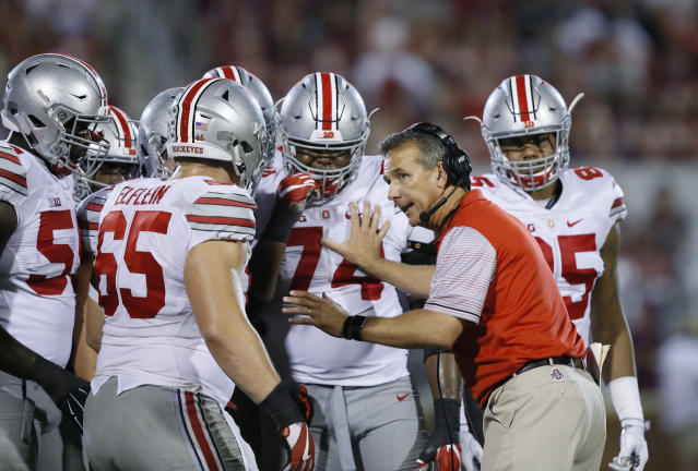 FILE - In this Sept. 17, 2016, file photo, Ohio State head coach Urban Meyer talks with his players in the fourth quarter of an NCAA college football game against Oklahoma, in Norman, Okla. Meyers current suspension and previous paid leave have restricted him from talking football with his staff and athletes during August with one exception _ a team meeting the day after the suspension was announced. Emails from the senior vice president for human resources show Meyer and athletic director Gene Smith were allowed to meet with the players and coaches last Thursday, Aug. 23, 2018. (AP Photo/Sue Ogrocki, File)