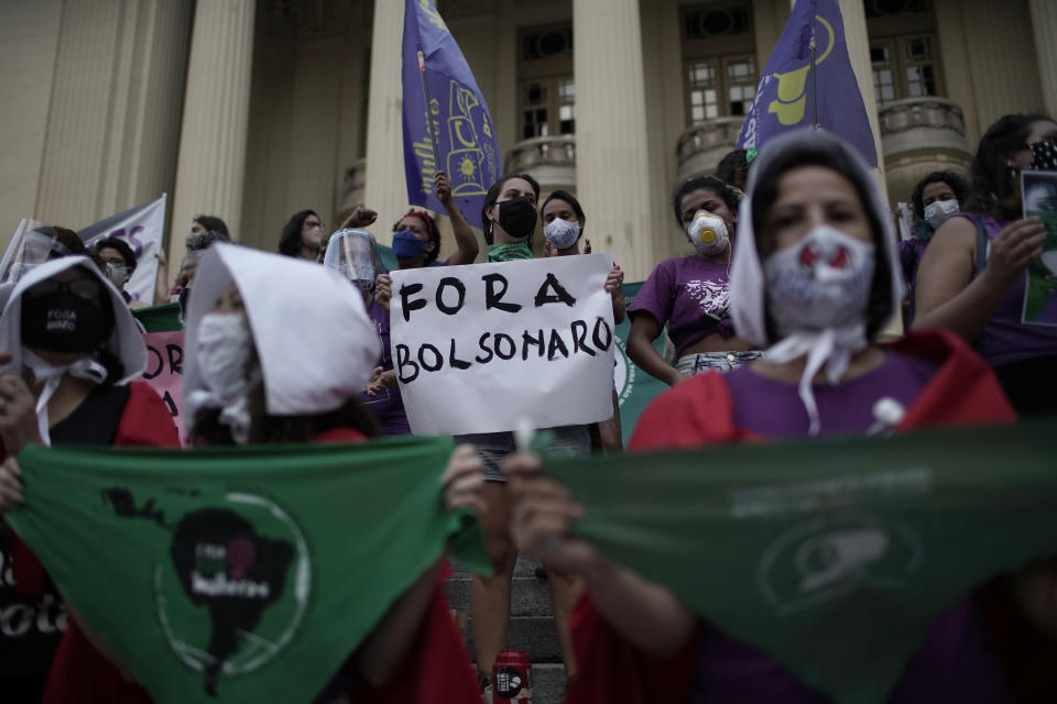 "FILE - In this Sept. 28, 2020 file photo, an abortion-rights protester holds a sign that reads in Portuguese ""Get out Bolsonaro"" directed at Brazilian President Jair Bolsonaro during a demonstration marking the ""Day for Decriminalization of Abortion in Latin America and the Caribbean,"" outside the state legislative assembly in Rio de Janeiro, Brazil, Monday, Sept. 28, 2020. Backed by Brazilian conservatives and evangelicals, lawmaker-turned-President Bolsonaro has said that if Congress legalized abortion, he would veto. (AP Photo/Silvia Izquierdo, File)"