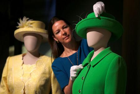 Curator Caroline de Guitar, poses for photographers next to Britain's Queen Elizabeth's green ensemble worn for Trooping the Colour in 2016 marking her official 90th birthday, ahead of the opening of an exhibition entitled 'Fashioning a Reign: 90 Years of Style from the Queen's Wardrobe', at Buckingham Palace, in London, Britain July 21, 2016.  REUTERS/Peter Nicholls