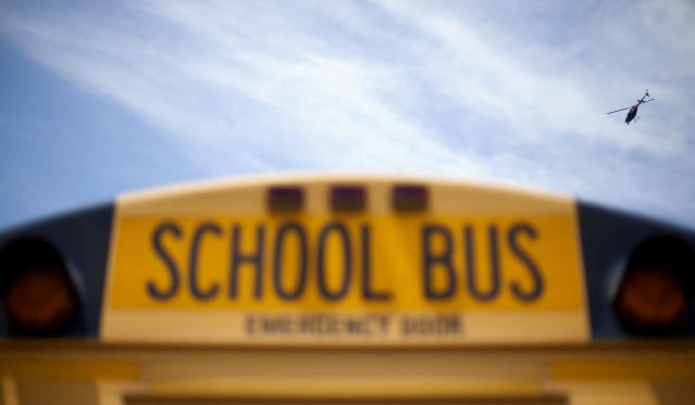 <p>A police helicopter hovers over a school bus as it drops off children outside a subdivision May 16, 2012, in Hampton, Ga. Police in an Atlanta suburb are escorting school buses and guarding students at bus stops after a man aimed a rifle at a bus with children on board and dropped a notebook that listed bus numbers. (AP Photo/David Goldman) </p>