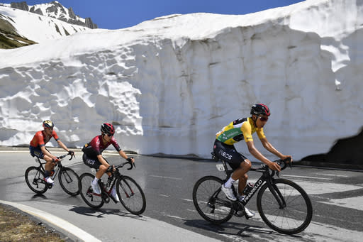 Rohan Dennis from Australia of Bahrain-Merida Pro Cycling Team, left, and Egan Bernal from Colombia of Team Ineos, right, climb the Nufenen pass during the ninth and final stage, a 101.5 km race with start and finish in Goms, Switzerland, at the 83rd Tour de Suisse UCI ProTour cycling race, on Sunday, June 23, 2019. (Gian Ehrenzeller/Keystone via AP)