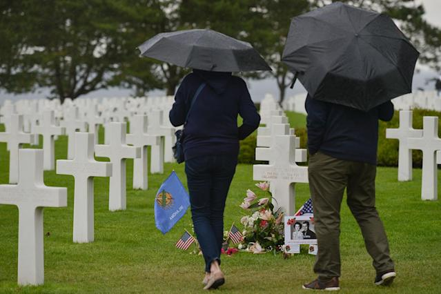 <p>Visitors view the graves of fallen soldiers at the Normandy American Cemetery, which contains the remains of 9,387 American military dead, most killed during the invasion of Normandy and ensuing military operations in World War II. (Photo: Artur Widak/NurPhoto via Getty Images) </p>