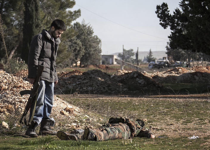 In this Saturday, Dec. 15, 2012 photo, a Free Syrian Army fighter looks at the lifeless body of a government troop killed during heavy clashes with government forces at a military academy besieged by the rebels north of Aleppo, Syria. Free Syrian Army fighters took control over the military academy after battling government forces for several hours. (AP Photo/Narciso Contreras)
