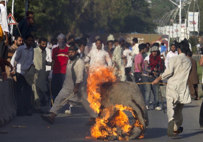 A Pakistani protester carries a burning piece of canvas towards containers police had placed to block the road leads to the diplomatic enclave in Islamabad, Pakistan on Thursday, Sept. 20, 2012. Hundreds of Pakistanis angry at an anti-Islam film that denigrates the religion's prophet clashed with police in the Pakistani capital Thursday, the most violent show of anger in a day that saw smaller demonstrations in Indonesia, Iran and Afghanistan. (AP Photo/B.K. Bangash)