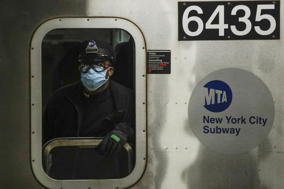 FILE - In this April 7, 2020, file photo, an MTA worker wears personal protective equipment at the Grand Army Plaza station in the Brooklyn borough of New York. As the coronavirus tightened its grip across the country, it is cutting a particularly devastating swath through an already vulnerable population, black Americans. (AP Photo/Frank Franklin II, File)