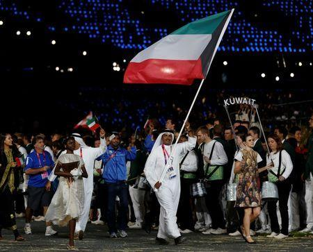 Kuwait's flag bearer Fehaid Aldeehani holds the national flag as he leads the contingent in the athletes parade during the opening ceremony of the London 2012 Olympic Games at the Olympic Stadium July 27, 2012. REUTERS/Murad Sezer