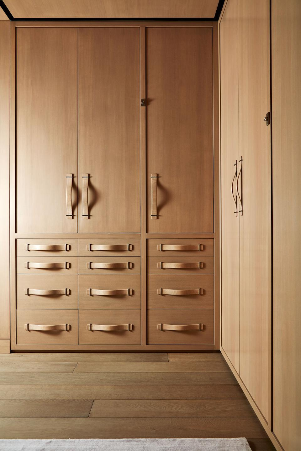 Bleached beechwood cupboards with carved handles line the dressing room.