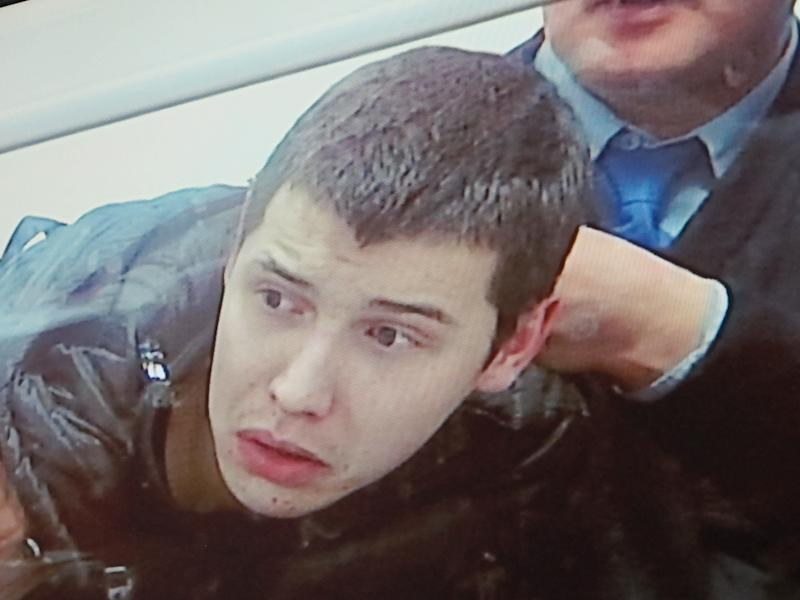 This photo of a relayed televised image from a courtroom shows Vladislav Chelakh struggling with guards Tuesday, Dec. 11, 2012, during the last day of his trial in the southern Kazakhstan city of Taldykorgan. Chelakh, a conscript in Kazakhstan's army, is accused of killing 14 fellow soldiers and a park ranger in a May massacre that shocked the Central Asian nation. (AP Photo/Peter Leonard)