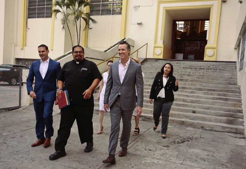 California Gov. Gavin Newsom, second from right, walks out with San Salvador Mayor Ernesto Muyshondtof, far left, after they visited the tomb of Archbishop Oscar Romero at Metropolitan Cathedral in San Salvador, El Salvador, Sunday, April 7, 2019. Behind are, from left, Karla Belismelis de Muyshondt, Jennifer Siebel Newsom, California state Assemblywoman Wendy Carrillo. (AP Photo/Salvador Melendez)