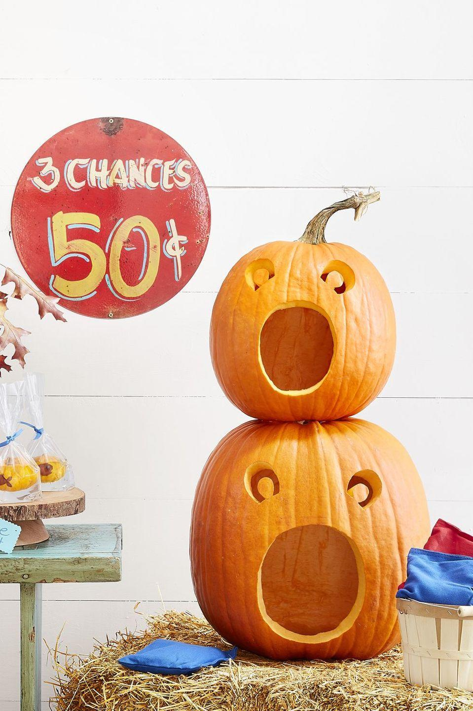 """<p>This year, get two spooky season activities for the price of one: <a href=""""https://www.goodhousekeeping.com/holidays/halloween-ideas/g238/pumpkin-carving-ideas/"""" rel=""""nofollow noopener"""" target=""""_blank"""" data-ylk=""""slk:carve your pumpkins"""" class=""""link rapid-noclick-resp"""">carve your pumpkins</a> into a fun bean-bag toss. To make this game, cut a large hole in the bottom of one large and one medium pumpkin and scoop out the pulp and seeds. Trace this <a href=""""https://hmg-prod.s3.amazonaws.com/files/pumpkin-carving-template-beanbag-toss-1018-1536169820.pdf"""" rel=""""nofollow noopener"""" target=""""_blank"""" data-ylk=""""slk:face template"""" class=""""link rapid-noclick-resp"""">face template</a> onto the pumpkins, scaling up or down as necessary. Cut out the faces, and then stack the medium pumpkin on top of the large one, using skewers to help hold them in place. </p><p>To play, toss beanbags into the pumpkins' mouths and award 10 points for the bottom gourd and 20 for the top.</p><p><strong>RELATED: </strong><a href=""""https://www.goodhousekeeping.com/holidays/halloween-ideas/g22062770/halloween-crafts-for-kids/"""" rel=""""nofollow noopener"""" target=""""_blank"""" data-ylk=""""slk:20+ Easy and Creative Halloween Crafts for Kids That You Can Make as a Family"""" class=""""link rapid-noclick-resp"""">20+ Easy and Creative Halloween Crafts for Kids That You Can Make as a Family</a></p>"""
