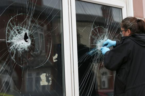 A police officer collects forensic evidence from the broken window of a mosque in Albert Road, Birmingham (PA)