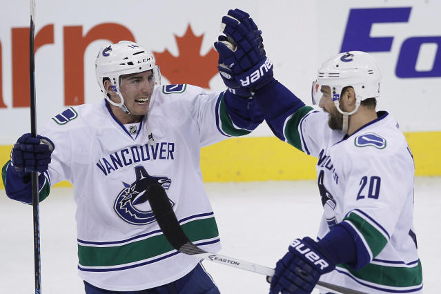 Vancouver Canucks' Chris Higgins (20) and Alexandre Burrows (14) celebrate Higgins' shootout goal against the Winnipeg Jets in an NHL hockey game Wednesday, March 12, 2014, in Winnipeg, Manitoba. The Canucks won 3-2. (AP Photo/The Canadian Press, John Woods)
