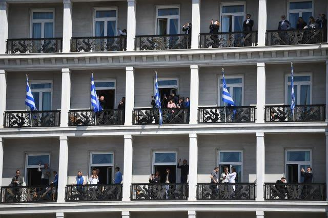 People watch from balconies of a building overlooking the Independence Day Military Parade in Syntagma Square