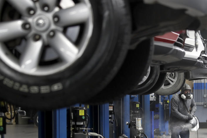 Elliot Nelson uses a fogger to disinfect a repair shop at a car dealership Wednesday, May 13, 2020, in Merriam, Kan. Nelson's business of cleaning car dealerships has expanded in recent months to include more surface disinfecting services to help stop the spread of COVID-19. (AP Photo/Charlie Riedel)