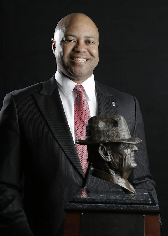 """Stanford coach David Shaw, a finalist for the Paul """"Bear"""" Bryant college coach of the year award, poses with the trophy Wednesday, Jan. 15, 2014, in Houston. (AP Photo/Pat Sullivan)"""
