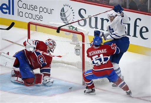 Montreal Canadiens goaltender Carey Price, left, is scored on by Toronto Maple Leafs' Korbinian Holzer, right, as Canadiens' David Desharnais defends during the third period of an NHL hockey game in Montreal, Saturday, Feb. 9, 2013. (AP Photo/The Canadian Press, Graham Hughes)