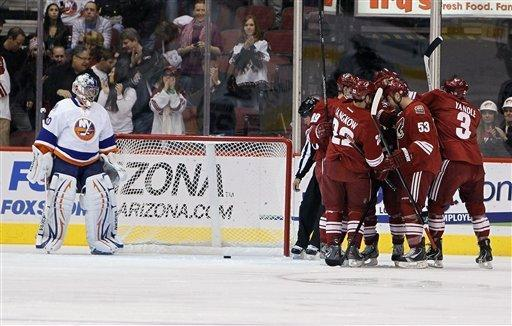 Phoenix Coyotes' Daymond Langkow (22), Derek Morris (53) and Keith Yandle (3) join other teammates in celebrating a goal by Coyotes' Shane Doan against New York Islanders' Evgeni Nabokov, left, of Russia, during the first period in an NHL hockey game on Saturday, Jan. 7, 2012, in Glendale, Ariz. (AP Photo/Ross D. Franklin)