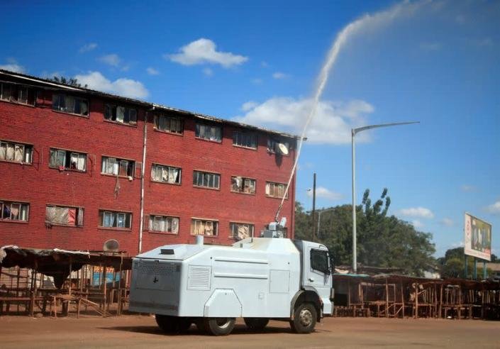A police water canon sprays disinfectant over residential flats during a 21-day nationwide lockdown called to help curb the spread of coronavirus disease (COVID-19), in Harare