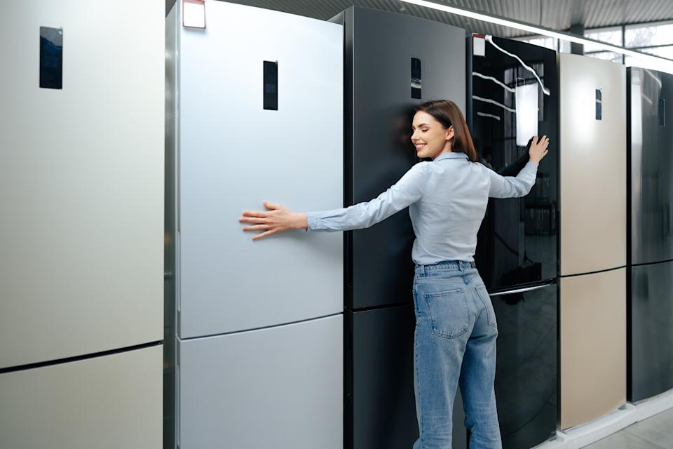 Young happy woman leaning on her new refrigerator in a shopping mall