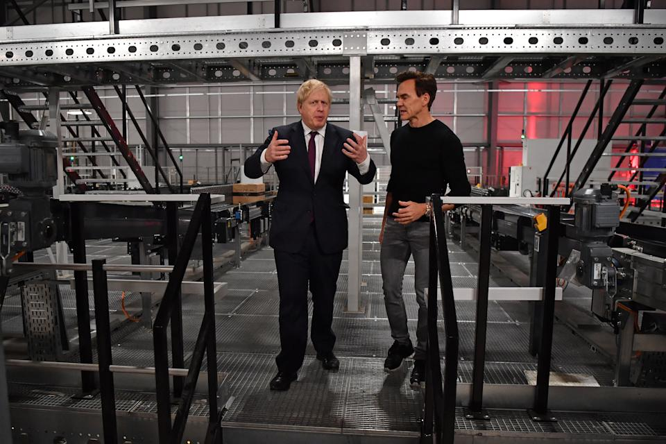 WARRINGTON, ENGLAND - DECEMBER 10: Britain's Prime Minister and Conservative party leader Boris Johnson (L) is shown around by company founder Matthew Moulding (R) during a visit to a fulfillment centre for The Hut Group (THG) during a general election campaign event on December 10, 2019 in Warrington, United Kingdom. The U.K will go to the polls in a general election on December 12. (Photo by Ben Stansall - WPA Pool / Getty Images)