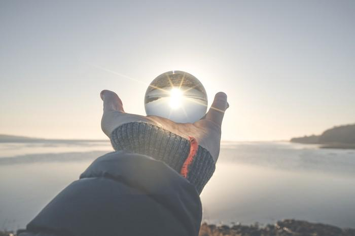 A hand holding a crystal ball toward the horizon
