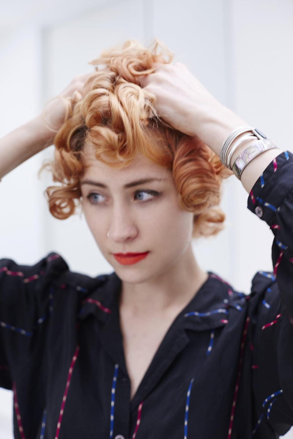 <p>Once all of the pins are removed, it's time to break up the curls. The best way to do this is by placing your hands underneath your hair, just behind your ears, and shaking it out at the root. You disrupt the curl less and the hair falls much more naturally.</p>