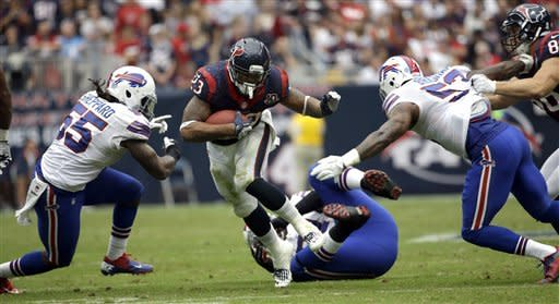 Houston Texans running back Arian Foster (23) rushes for a gain as Buffalo Bills middle linebacker Kelvin Sheppard (55) and Nigel Bradham (53) defend in the third quarter of an NFL football game on Sunday, Nov. 4, 2012, in Houston. The Texans defeated the Bills 21-9. (AP Photo/David J. Phillip)
