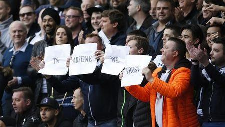 Tottenham fans hold up banners for Arsenal manager Arsene Wenger