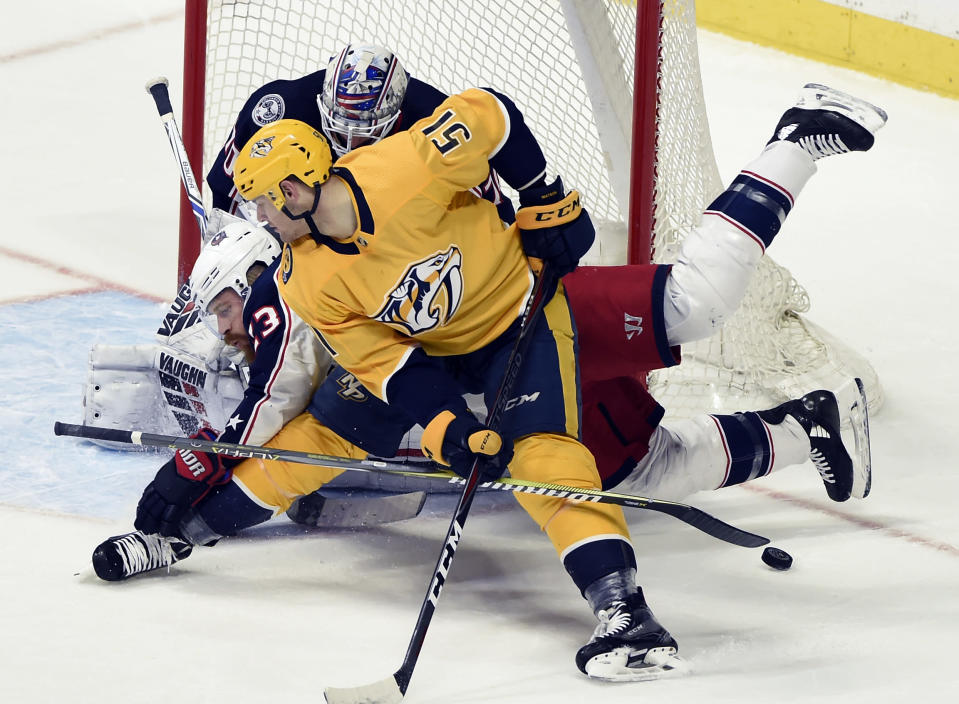 Nashville Predators left wing Austin Watson (51) and Columbus Blue Jackets defenseman Ian Cole (23) battle for the puck in front of Blue Jackets goaltender Joonas Korpisalo, top, of Finland, during the first period of an NHL hockey game Saturday, April 7, 2018, in Nashville, Tenn. (AP Photo/Mark Zaleski)
