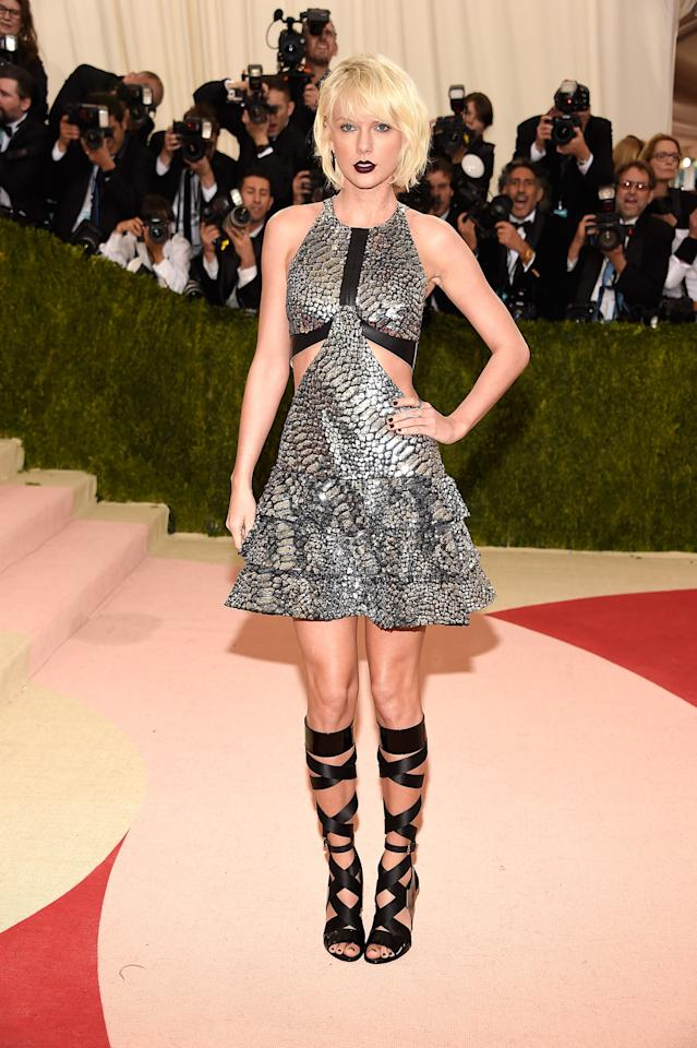 <p>Fully embracing Anna Wintour's advice to give grunge a try, Taylor Swift attended the Met Gala in a silver mini dress made of fabric reminiscent of a reptile's skin. Made with a halter neckline and flare skirt, the piece also featured cutouts. Her lace-up ribbon heels added some girliness to an otherwise hard look, which was completed with a messy platinum-blonde bob and dark lip. <i>(Photo: Getty Images)</i></p>