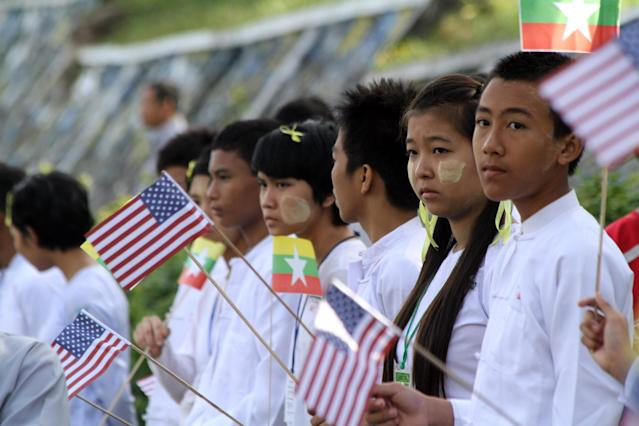 Myanmar students hold Myanmar and U.S. flags as they wait to welcome the arrival of U.S. President Barack Obama at Yangon International Airport Monday, Nov. 19, 2012, in Yangon, Myanmar. (AP Photo/Khin Maung Win)
