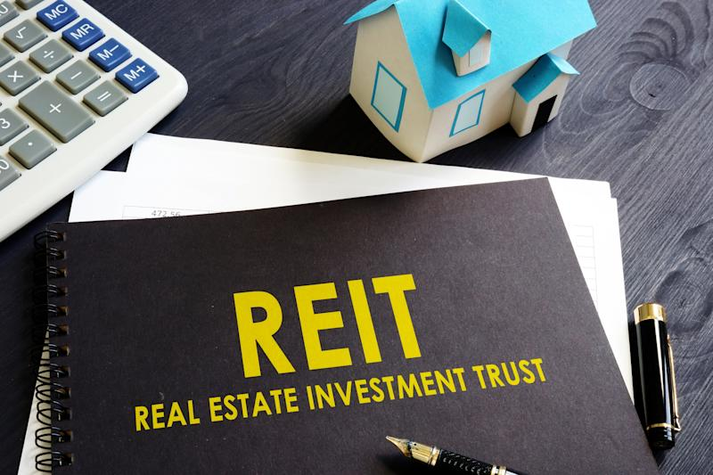 "The acronym REIT with the words ""real estate investment trust"" written out underneath on the front of a binder."