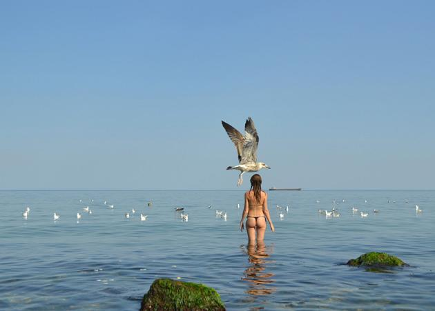 A seagull passes a girl preparing to refresh herself during 35C heat in Black Sea willage of Zatoka, some 60 km from the Ukrainian city of Odessa on August 5, 2012. AFP PHOTO/ SERGEI SUPINSKY