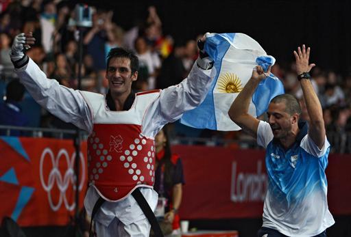 Argentina's Sebastian Eduardo Crismanich celebrates his victory over Spain's Nicolas Garcia Hemme at the end of their men's  taekwondo gold medal bout  in the category  under 80 kg as part of the London 2012 Olympic games, on August 10, 2012 at the ExCel centre in London.  AFP PHOTO / TOSHIFUMI KITAMURA