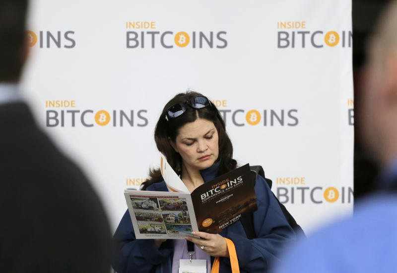 A woman reads about bitcoin while attending the Inside Bitcoins conference and trade show, Monday, April 7, 2014 in New York. Bitcoin users exchange cash for digital money using online exchanges, then store it in a computer program that serves as a wallet. The program can transfer payments directly to merchants or individuals around the world, eliminating transaction fees and the need for bank or credit card information. (AP Photo/Mark Lennihan)